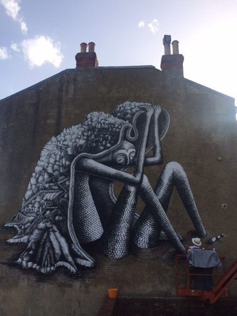 Artist Phlegm at work on his Ventnor Street Art, the mournful giant with Ventnor on his shoulders.