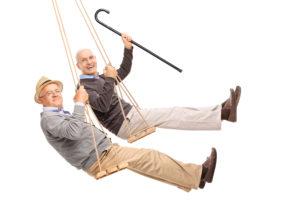 Two cheerful elderly men on wooden swings