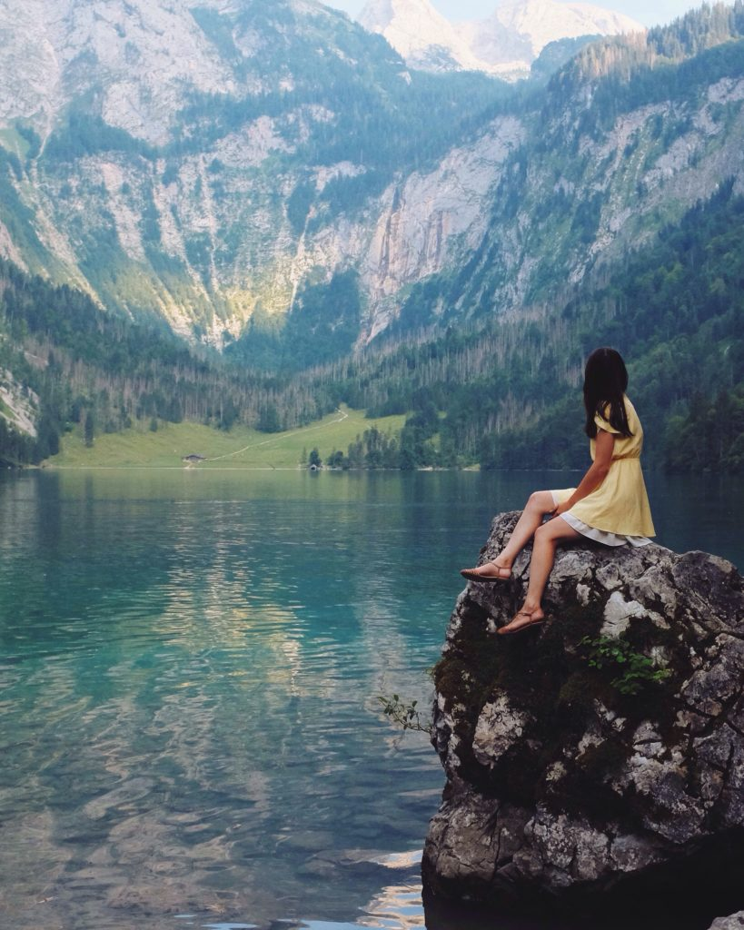 A girl perched on a rock looking out at a lake and mountains, Picture by Nadi Whatisdelirium