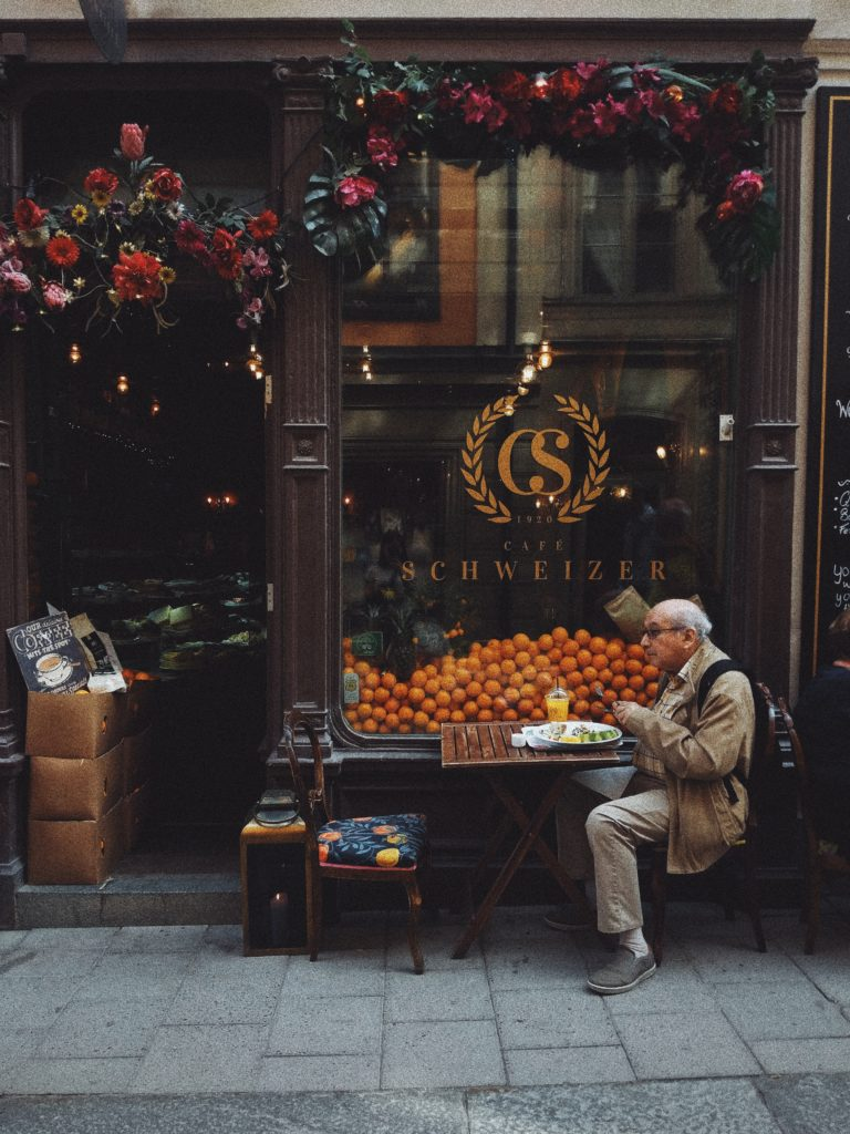 Man eating breakfast at a pavement cafe, picture by Olena Sergienko