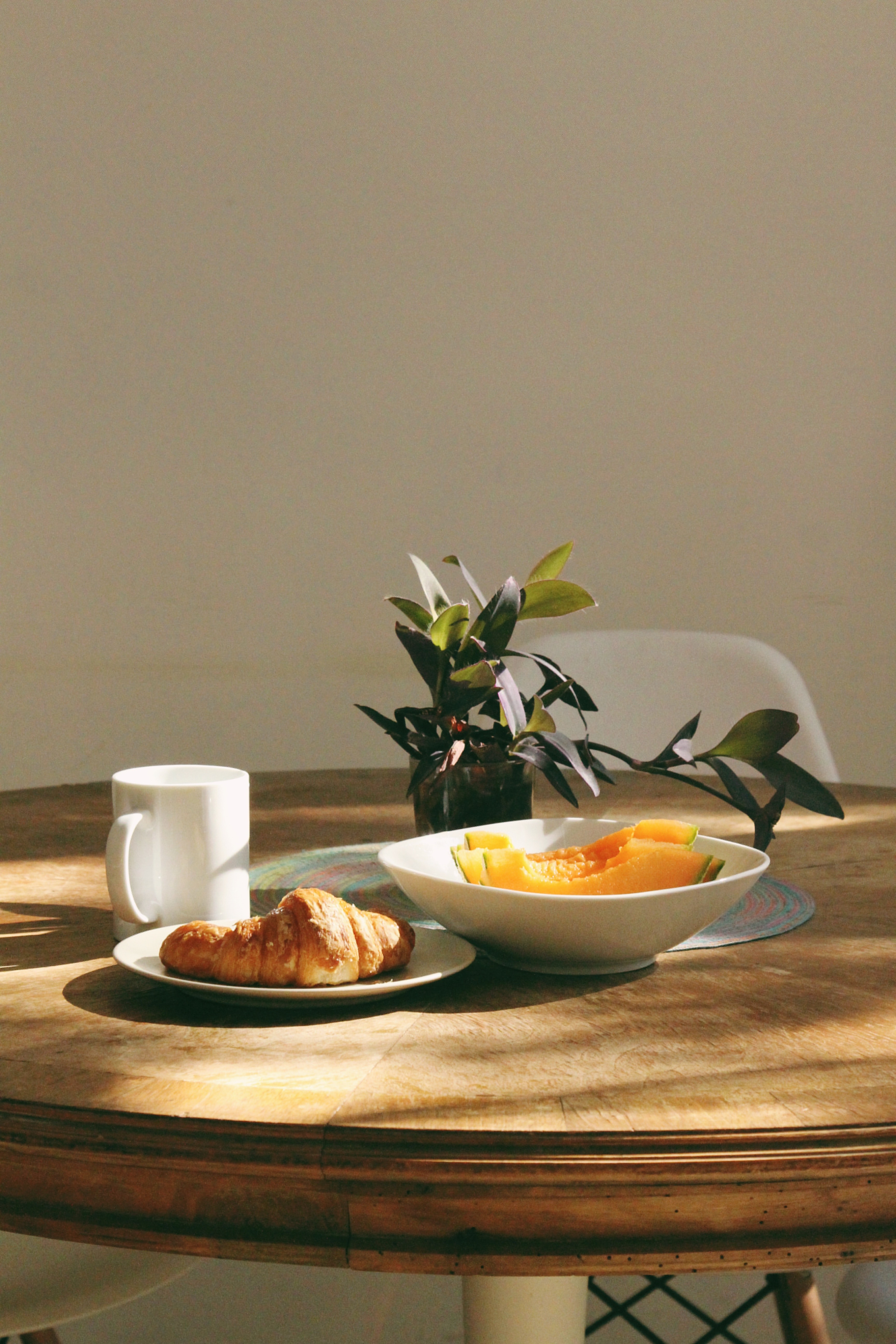 A breakfast sits of a white mug of coffee, a croissant, and two slice of cantaloupe sit on a wooden table alit in morning sunshine with a green plant as centrepiece. Photo by Tatiana from Pexels.