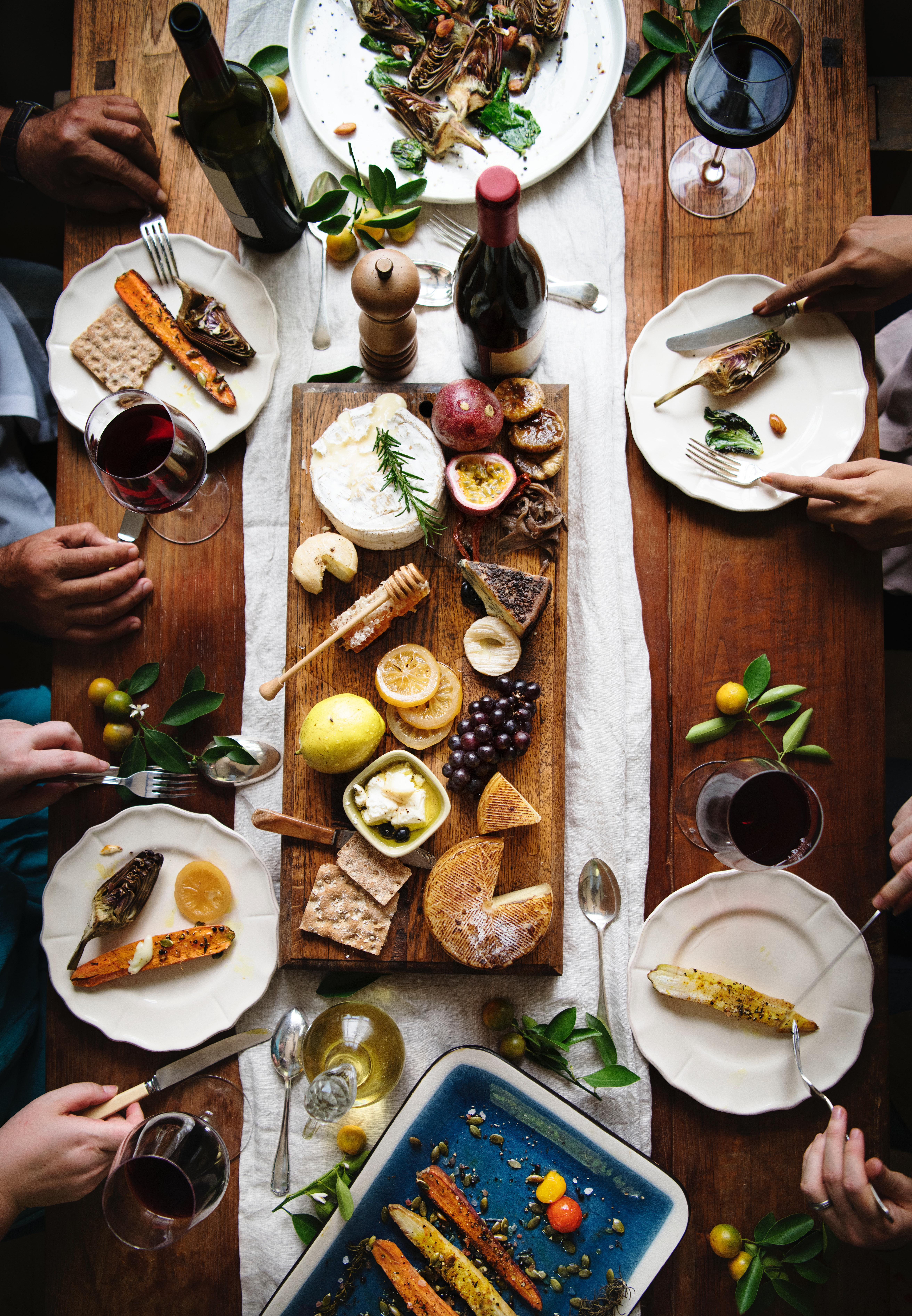 Shot from above, a group of four people share a plate of cheeses, fruit, grilled veggies, and red wine. Photo by rawpixel.com from Pexels.