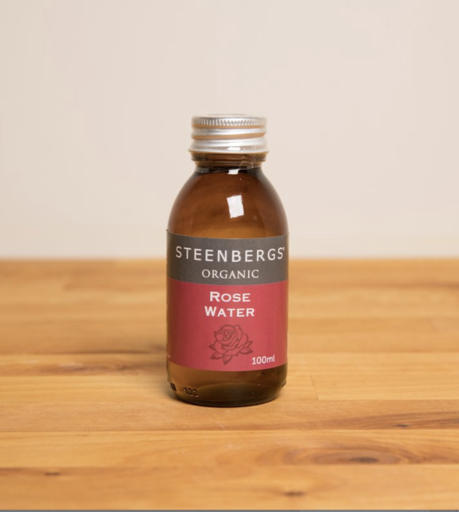A 100ml brown bottle with a red, grey, and white label reading 'Steenbergs' Organic Rose Water' is contained by a silver twist cap. The bottle sits on a light-coloured wooden table with a grey wall behind it.