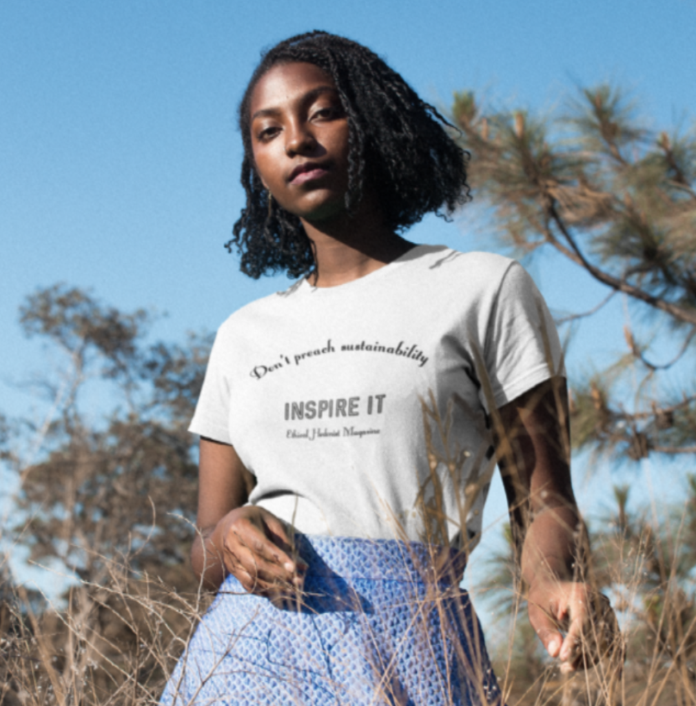 A model wears the fitted 'Don't Preach Sustainability, Inspire It' t-shirt made in collaboration between Teemill and Ethical Hedonist. She is outdoors in front of tall trees with tall grass in front of her.