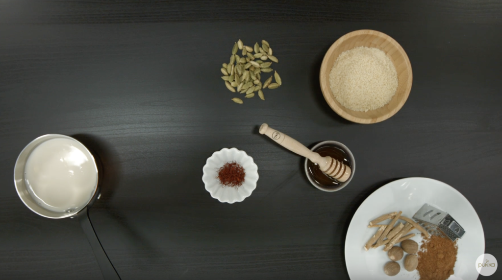 A flat-lay of all the ingredients required for the Golden Milk of Bliss recipe, including cardamom pods, crushed almonds, honey, saffron, ashwagandha root, nutmeg, turmeric root powder, and almond milk.