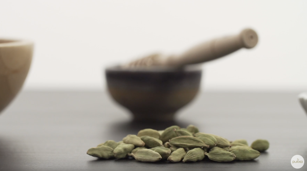 A close-up of cardamom pods with a blurred bowl of honey in the background.