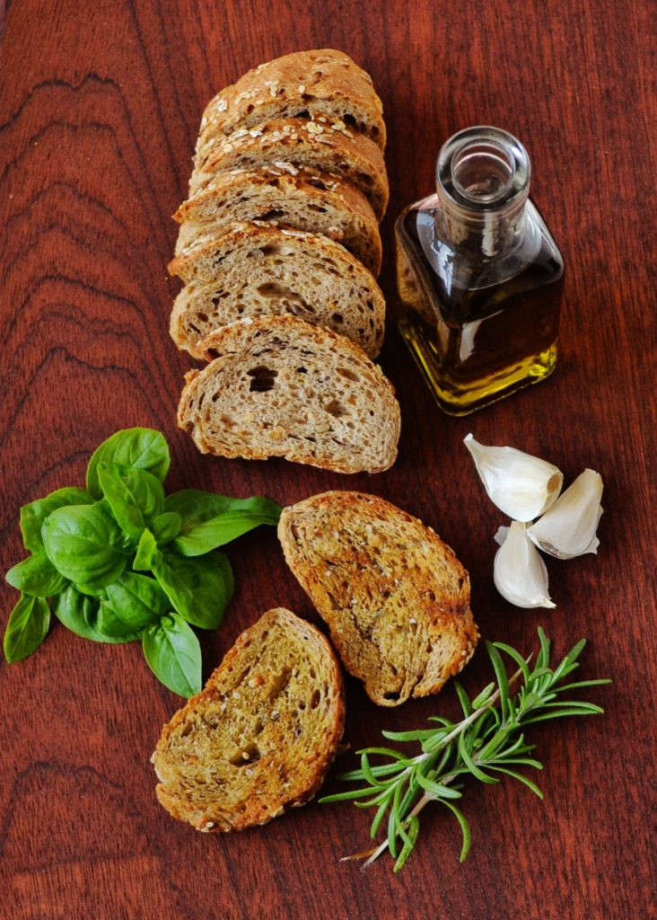 Organic olive oil and fresh baked bread presented with basil, rosemary, and garlic. Photo by Dana Tentis from Pexels.