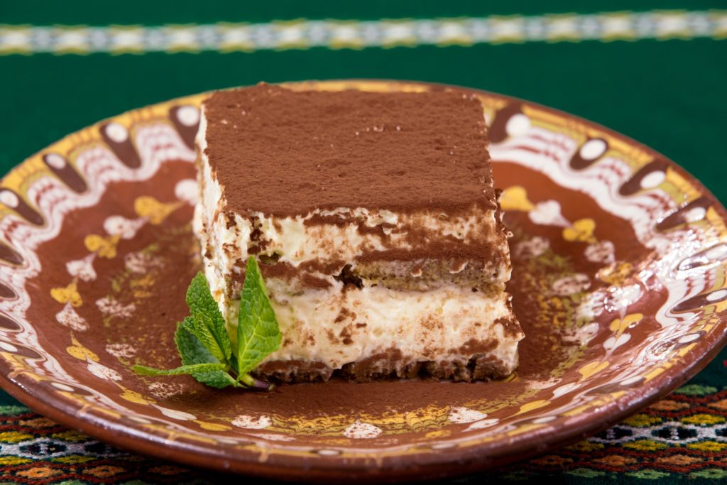 A piece of tiramisu on a brown and yellow plate. Image by pastel100 from Pixabay.